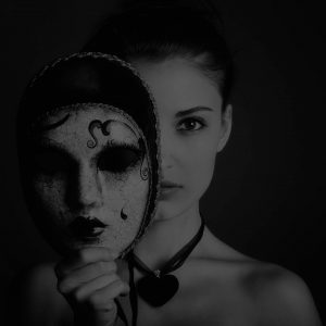 Taylor image International model holding a mask. in front of her face .
